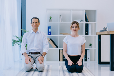 businessman with his trainer meditating on yoga mats at office Stock Photo