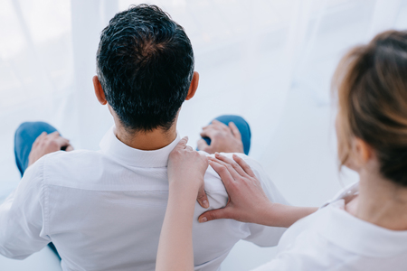 high angle view of masseuse doing seated shoulder massage for businessman