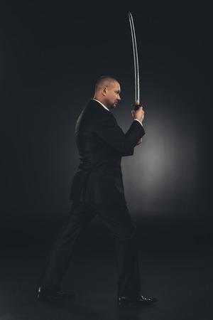 side view of yakuza member in suit with katana sword on black