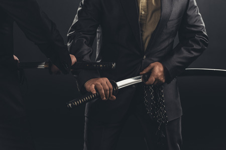 cropped shot of modern samurai taking out their swords isolated on black