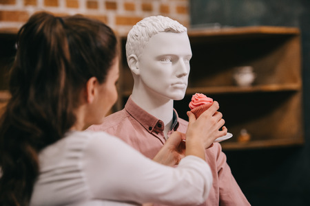 woman pretending to feed mannequin with cupcake at home, perfect relationship dream concept