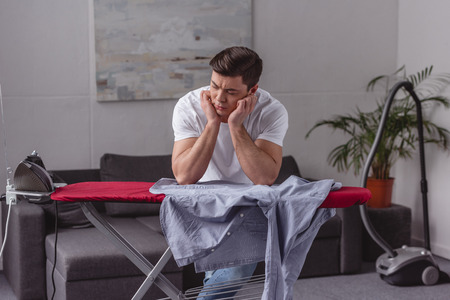 man resting chin on hands and looking at iron in living room