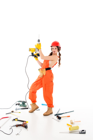 workwoman in overalls with electric drills, different tools lying on floor, isolated on white
