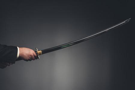 cropped shot of man holding katana sword on black