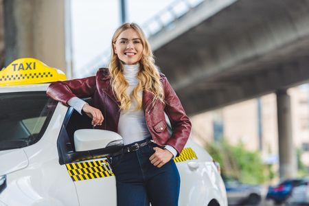 beautiful blonde girl leaning at taxi cab and smiling at camera