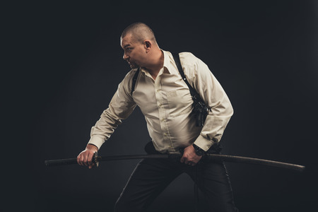 yakuza member taking out his katana sword