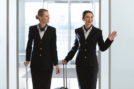 happy young stewardesses at departure area of airport with suitcases