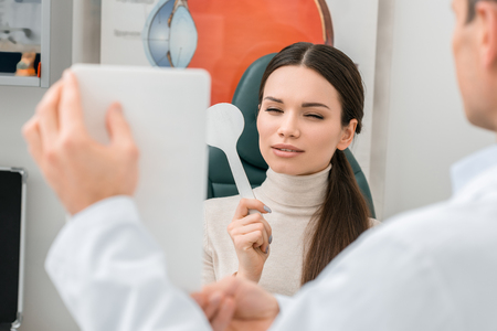 partial view of young woman getting eye test by oculist in clinic Stock Photo