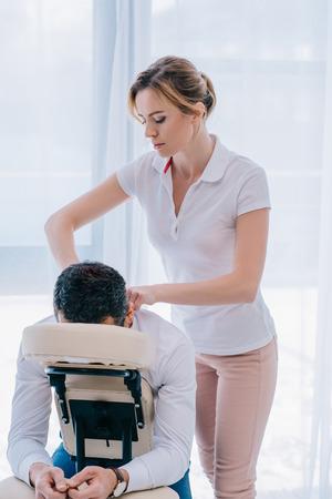 atrakcyjna masażystka wykonująca masaż ramion na siedzeniu w biurze Zdjęcie Seryjne