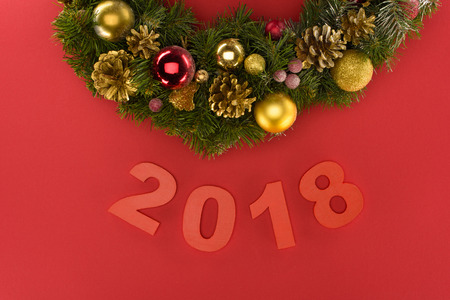 close up view of 2018 year sign and festive christmas decorations isolated on red