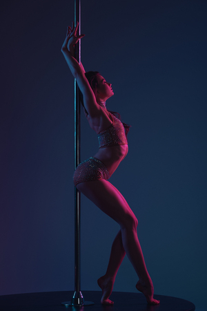 side view of seductive young female dancer leaning at pole on blue Stok Fotoğraf - 114331073