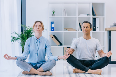 businesswoman with her trainer meditating in lotus pose at office Stock Photo