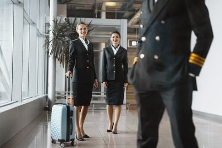 stewardesses looking at pilot at airport lobby before flight