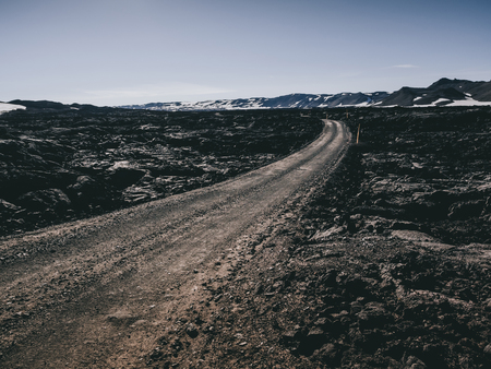 scenery with road and black rocks and mountains in Iceland Stock Photo