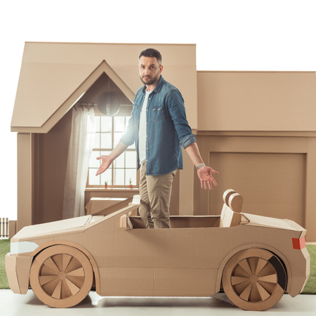 handsome man in cardboard car in front of cardboard house isolated on white