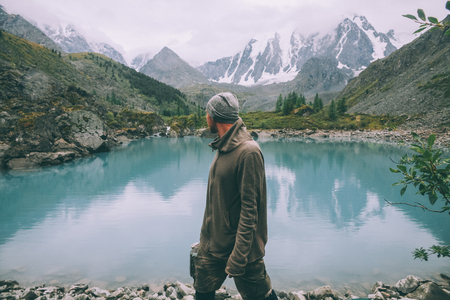 side view of man looking at majestic calm mountain lake in Altai, Russia 写真素材