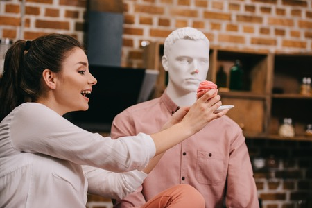 excited woman pretending to feed mannequin with cupcake at home, perfect relationship dream concept