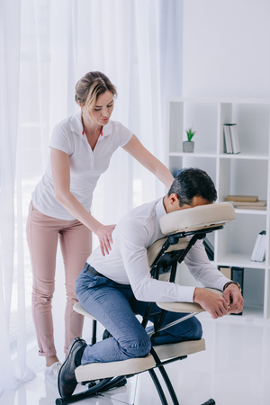 masseuse doing back massage for businessman at office