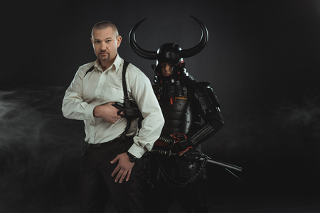 man with gun and armored samurai behind him on black Banco de Imagens