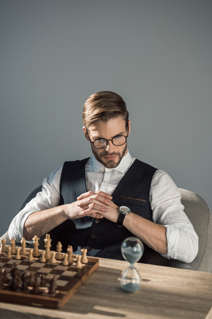 concentrated young businessman looking at sand clock while playing chess Stok Fotoğraf