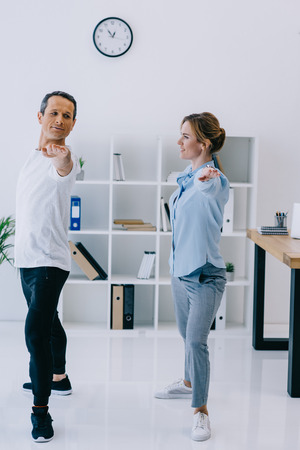 businesswoman doing exercise with trainer at office