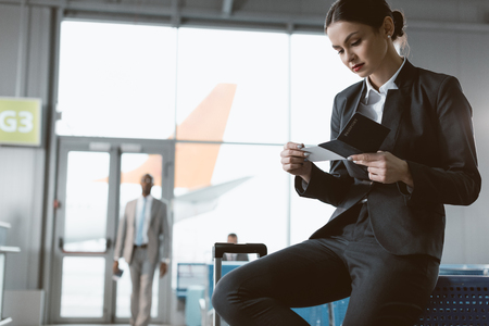 businessman discovering ticket while waiting for flight at airport lobby