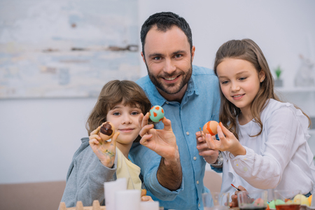father and kids showing easter eggs at camera