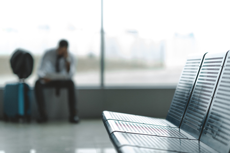 close-up shot of seats at airport lobby with buisnessman waiting for plane blurred on background Stock fotó
