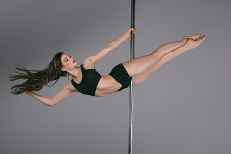 full length view of beautiful sporty girl dancing with pole on grey