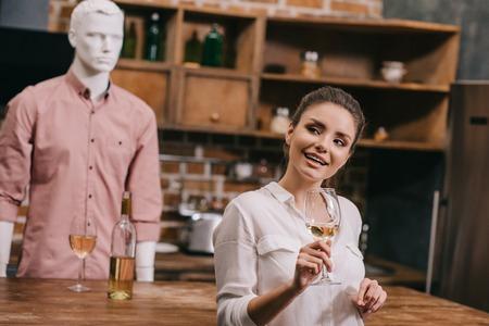 El enfoque selectivo de la mujer con copa de vino y maniquí en ropa casual en la cocina de casa, concepto de amor no correspondido Foto de archivo
