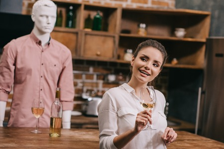 selective focus of woman with glass of wine and manikin in casual clothing in kitchen at home, unrequited love concept Zdjęcie Seryjne