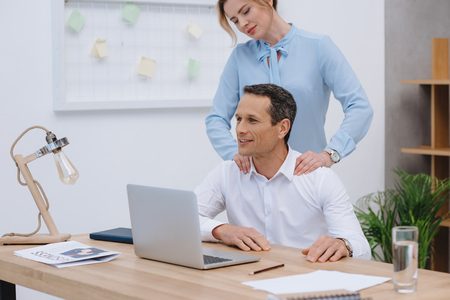 businessman working with laptop at workplace while woman doing massage for him Stock Photo