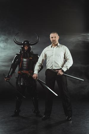 modern man and samurai with katana swords on black