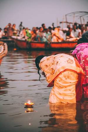 people perform ritual puja at dawn in the Ganges River in Varanasi, India Stock fotó
