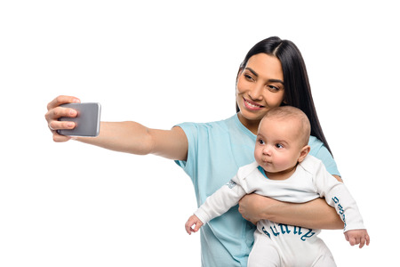 portrait of smiling mother taking selfie together with little baby isolated on white