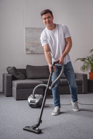 handsome man cleaning living room with vacuum cleaner