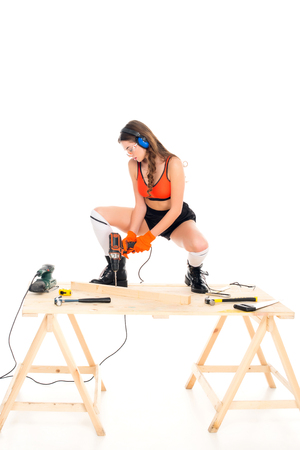 seductive girl in protective headphones working with electric drill at wooden table with tools, isolated on white