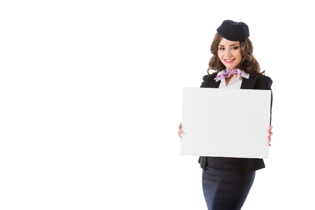 smiling attractive stewardess holding empty board isolated on white Foto de archivo