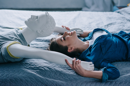 side view of smiling woman and mannequin lying on bed, loneliness concept Foto de archivo