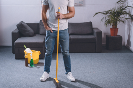 cropped image of man standing with broom in living room