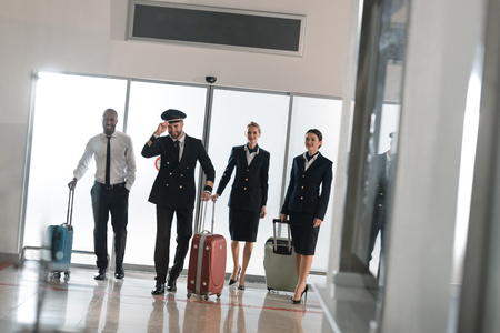 aviation personnel team walking by airport loggy with suitcases