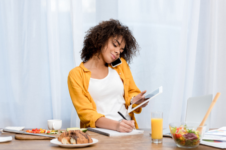young african american woman working at home during breakfast Stockfoto