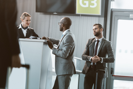 queue of businessmen at airport reception to buy tickets Stockfoto