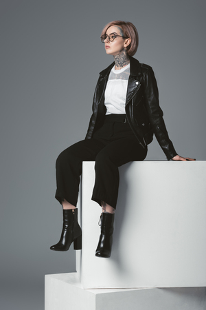 beautiful young tattooed woman in leather jacket sitting on white cubes and looking away isolated on grey