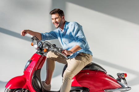 side view of young cheerful man sitting on red scooter
