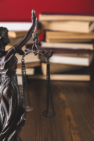 statue lady justice on wooden table with books, law concept Фото со стока