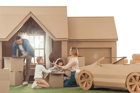 Jeune famille emménageant dans une nouvelle maison en carton isolée sur blanc