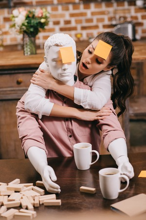 portrait of woman with sticky note on forehead hugging layman doll at home, perfect relationship dream concept Foto de archivo