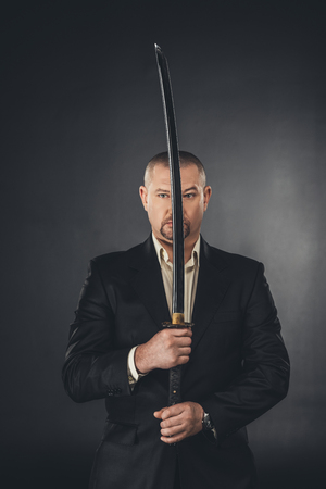 man in suit holding katana sword in front of his face on black Stock Photo