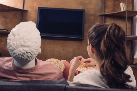 back view of woman eating popcorn while watching film together with manikin at home, perfect relationship dream concept
